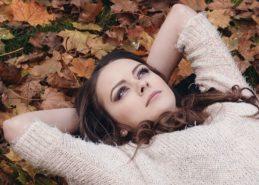 Młoda kobieta leży wśród jesiennych liści
