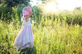Obrazek przedstawia dziewczynkę w kapeluszu. Dziewczynka sto na lące, ręką przytrzymuje różowy kapelusz.