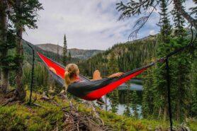 Na obrazku kobieta leżąca na hamaku. W tlw panorama gór i jezioro.